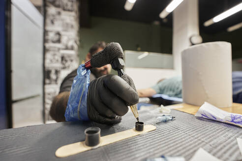 Close-up of male artist dipping tattoo machine in ink on table - SASF00098