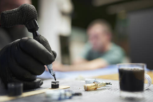 Hand of male artist dipping tattoo machine in ink on table - SASF00101