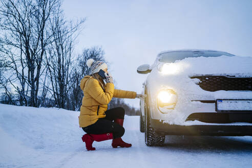 Mature woman talking over smart phone while crouching car on snow covered land - DGOF01429