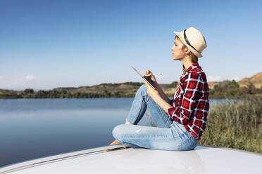 Woman using digital table while sitting on car roof - JSRF01137