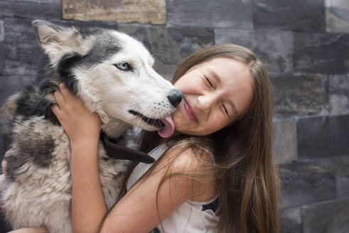 Girl embracing dog while sitting against wall - DSIF00133