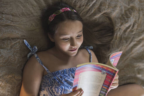 Girl smiling while reading book in bed at home - DSIF00139