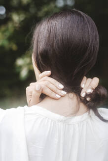 Close-up of mid adult woman holding hair - EYAF01312