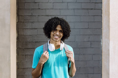 Young man standing with headphone against brick wall - XLGF00492