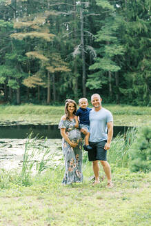 A happy growing family standing by a pond - CAVF89219