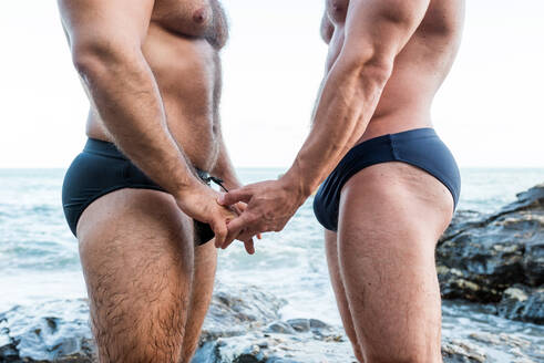 Lgbt pride concept. Muscled male gay couple holding hands detail. Seascape. - CAVF89267