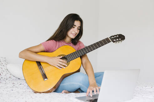 Lleida, Catalonia, Spain - Young woman learning to play guitar online - XLGF00541