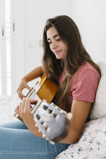Young woman playing guitar at home in bedroom - XLGF00544