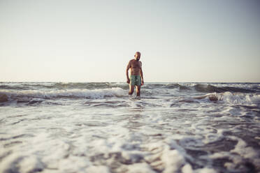 Man walking in water at beach during sunset - MEUF02070