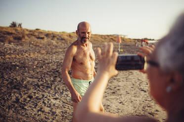 Senior woman taking photo of man standing at beach - MEUF02073