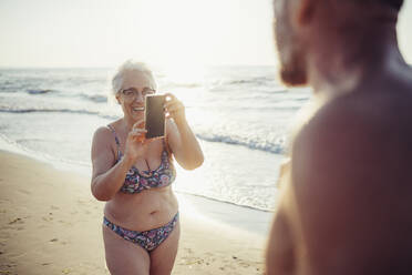 Senior woman in bikini taking photo of man while standing at beach - MEUF02076