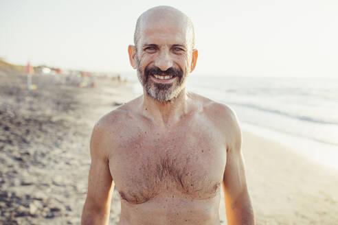 Smiling man standing at beach - MEUF02079