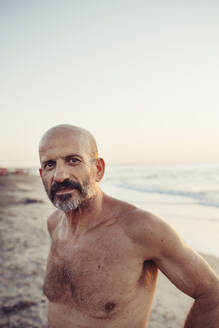 Shirtless senior man standing at beach - MEUF02082