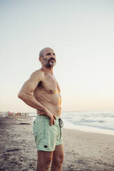 Man with hand on hip standing at beach during sunset - MEUF02085