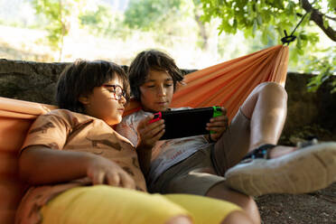 Siblings playing video games while lying on hammock at backyard - VABF03496