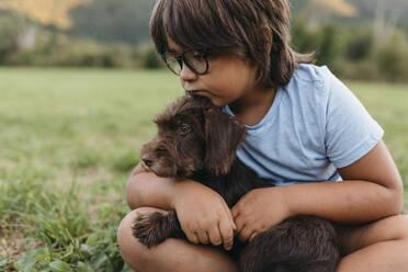 Boy sitting with dog on grass at backyard - VABF03508