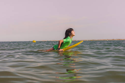 Carefree girl bodyboarding on sea against clear sky at sunset - ERRF04407