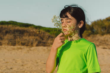 Cute girl with eyes closed smelling flowers while standing at beach against clear sky - ERRF04411