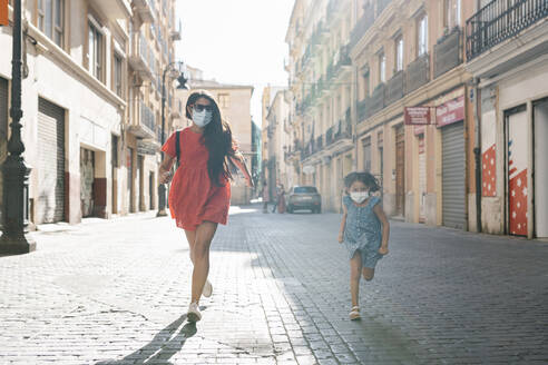 Cheerful mother and daughter wearing masks running on street in city - EGAF00737