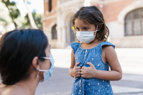 Girl wearing mask looking at mother while standing on street - EGAF00740