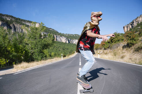 Man wearing dinosaur mask skateboarding on road against clear sky - PGF00017