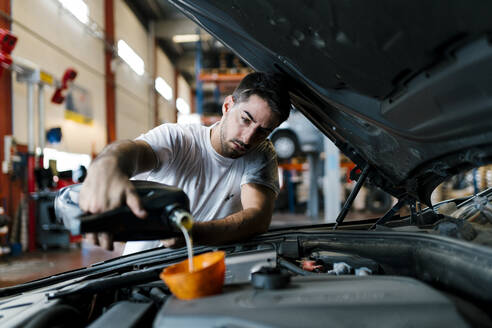 Auto mechanic filling engine oil while standing in garage - EGAF00788