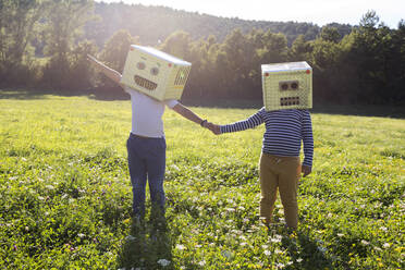 Boys face covered with box holding hands while standing on grass - VABF03514
