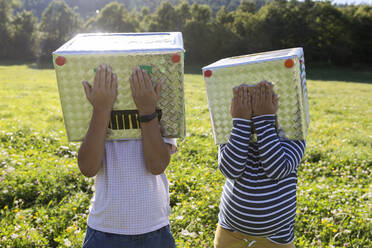 Boys covering cardboard box face with hand while standing in meadow - VABF03517