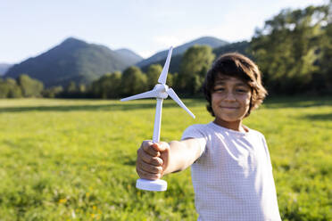 Smiling boy holding wind turbine toy while standing in meadow - VABF03532