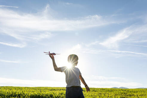 Playful boy holding airplane toy while standing against clear sky - VABF03538