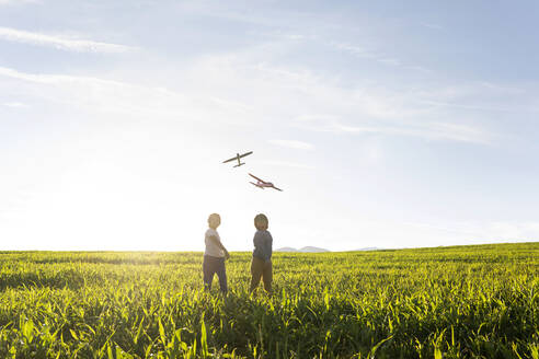 Boys looking at flying airplane toy while standing on grass in meadow - VABF03544