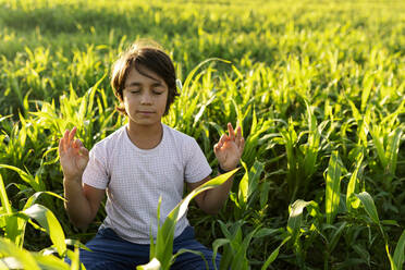 Boy meditating while sitting on grass in meadow - VABF03550