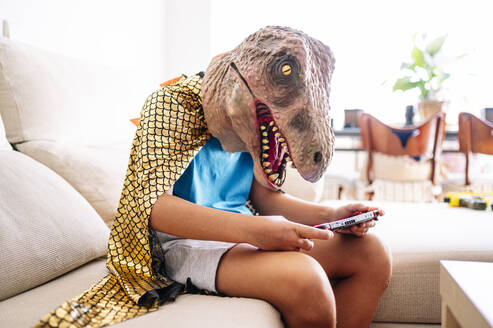Boy wearing dinosaur mask and cape using smart phone while sitting on sofa at home - JCMF01449