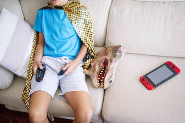 Boy watching TV while sitting by dinosaur mask on sofa at home - JCMF01452