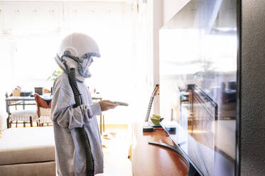 Boy wearing space helmet watching TV while standing at home - JCMF01461