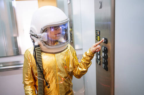 Boy wearing space suit pressing buttons in elevator - JCMF01473