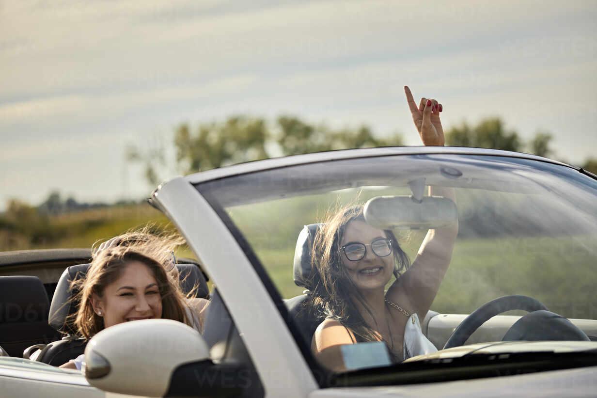 Cheerful Female Friends Enjoying Road Trip In Convertible Against Sky At Sunset Zedf03781 Zeljko Dangubic Westend61