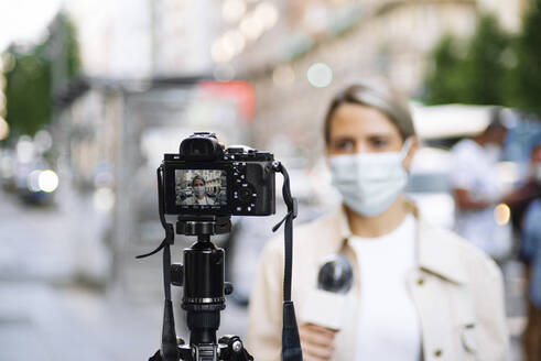 Female journalist wearing mask filming with camera in city - JCMF01484