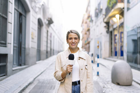 Female journalist talking over microphone while standing on street in city - JCMF01487