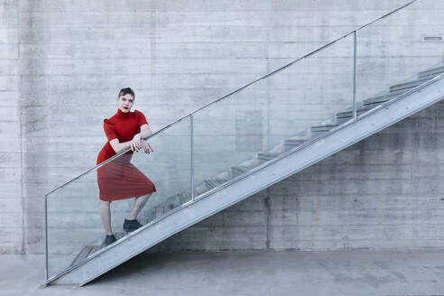 Portrait of non-binary person with red dress on urban stairs in Granada, Spain. gender fluid
