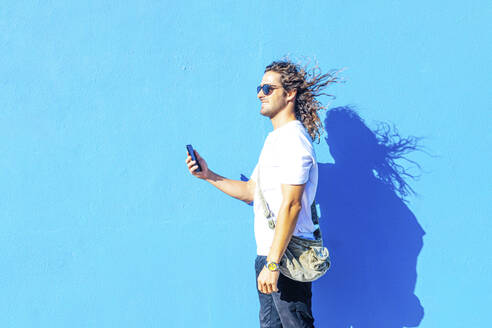 Smiling young man wearing sunglasses using smart phone while standing by blue wall - PGF00026