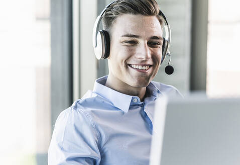 Close-up of smiling businessman talking over headset in call center - UUF21483