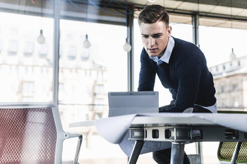 Male professional working over digital tablet while sitting on desk in office - UUF21519