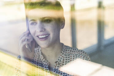 Close-up of female entrepreneur talking over mobile phone in office seen through window - UUF21522