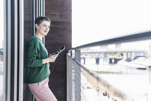 Thoughtful female professional with digital tablet standing in balcony at office - UUF21540