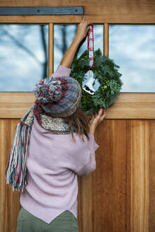 Young woman hanging wreath on house - LBF03233