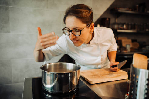 Female chef smelling hot food while cooking in restaurant kitchen - CAVF89272