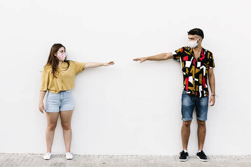 Young friends keeping social distancing while standing against wall - XLGF00587