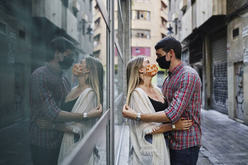 Refection of couple embracing with protective face mask while standing on street in city - SASF00109