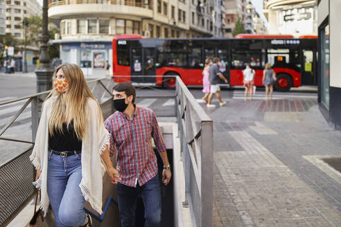 Couple wearing face mask climbing steps of subway in city - SASF00112